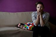 Aurora Salazar, de 19 anos, sentada con su bebe momentos antes de su intento de desahucio. Aurora y su esposo, Lazaro Romero, tienen dos hijos, Ainhoa de dos anos y un bebe de seis meses. Hace tres anos ocuparon un piso propiedad de la Empresa Municipal de la Vivienda y Suelo (EMVS). Lazaro trabajaba como vendedor de chatarra que apenas le daba ingresos. Tambien recibian una ayuda del Gobierno de 552 euros al mes.