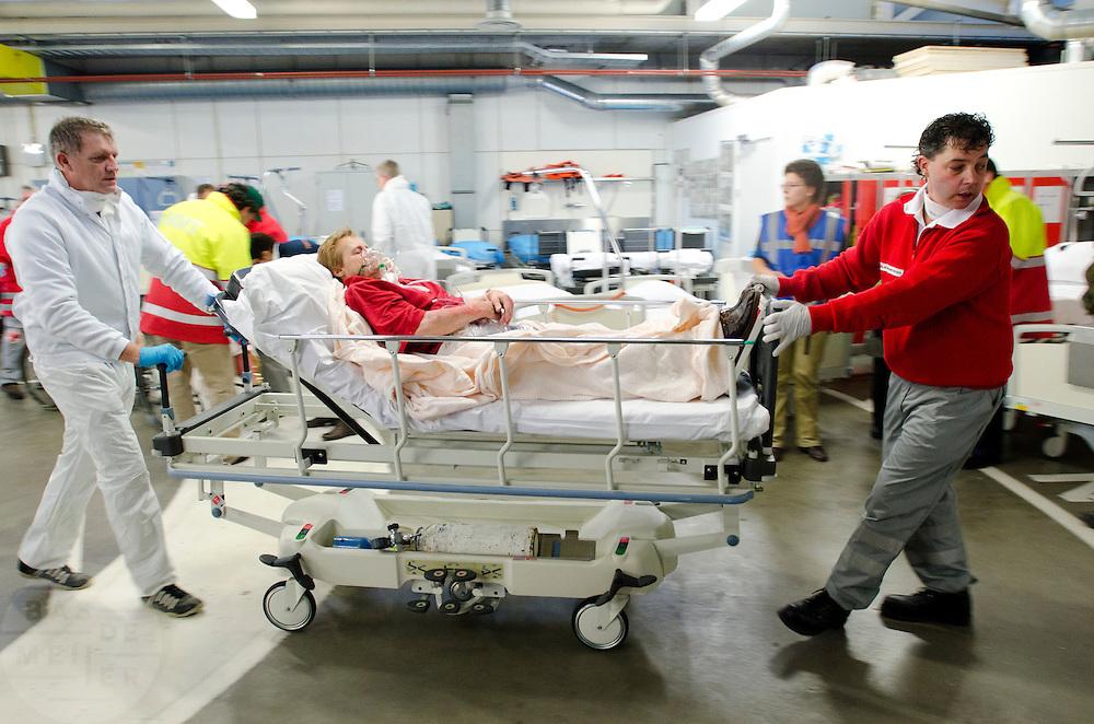 Een slachtoffer wordt op een ziekenhuisbed van de ambulancesluis naar het ziekenhuis vervoerd.  In het Calamiteitenhospitaal in Utrecht wordt een rampenoefening gehouden. De nadruk ligt op de contaminatie, door een gekantelde vrachtwagen zijn veel slachtoffers in aanraking gekomen met een chemische stof. Voor het eerst wordt er geoefend met een zogenaamde decontaminatietent. Als de tent bevalt, schaft het ziekenhuis zo'n tent aan. Bij de 'ramp' zijn 100 slachtoffers gevallen.<br /> <br /> A patient is transported to the hospital. In the Trauma and Emergency Hospital in Utrecht an calamity training was held. The emphasis is on the contamination by an overturned truck, many victims are contaminated by a chemical. For the first time a so-called decontamination tent was used. If the tent fulfills the expectations, a tent will be purchased. The 'calamity' caused 100 victims.