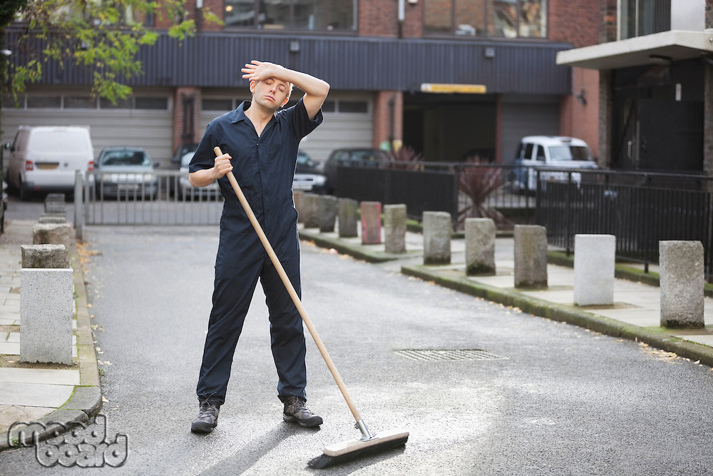 Tired young male street sweeper