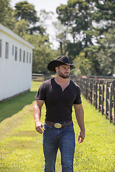 tough cowboy walking on a ranch