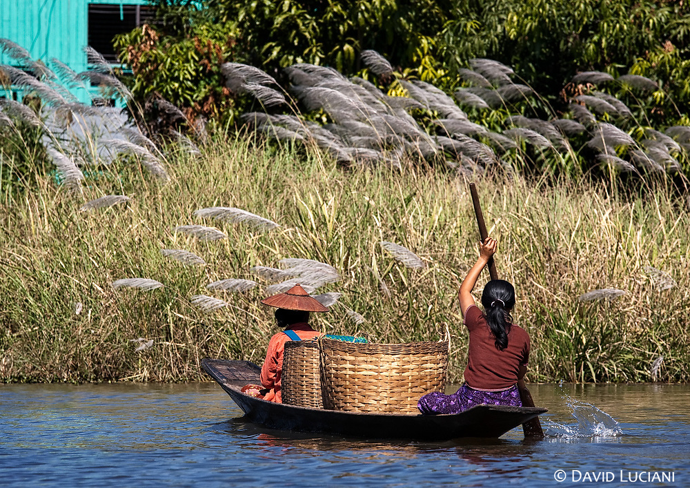 Two women transporting handwoven bamboo baskets with their boat.