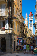 Tourists in by Spianada and Church of Saint Spyridon clock belltower, in Agiou Spiridonos Kerkyra, Corfu Town, Greece