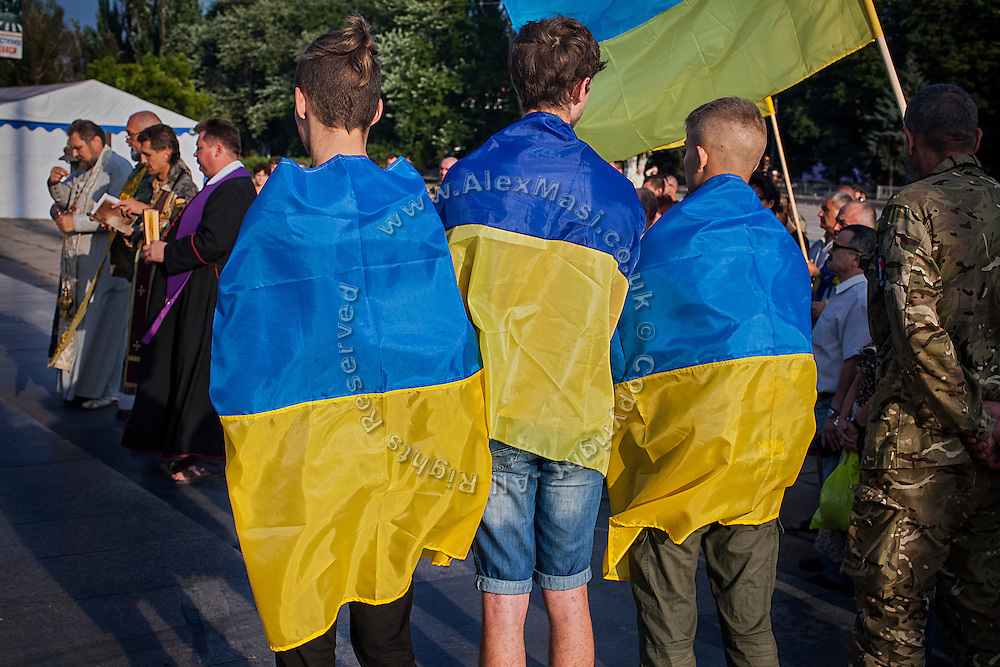 Members of the clergy, military men and Ukrainian patriots wearing the nation's flag, are attending a ceremony to commemorate recently killed soldiers during the Donbas war, in Mariupol, southeast Ukraine.