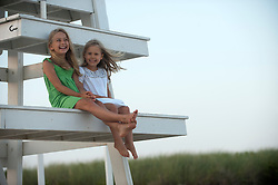 two girls enjoying themselves while seated on a lifeguard stand in East Hampton, NY