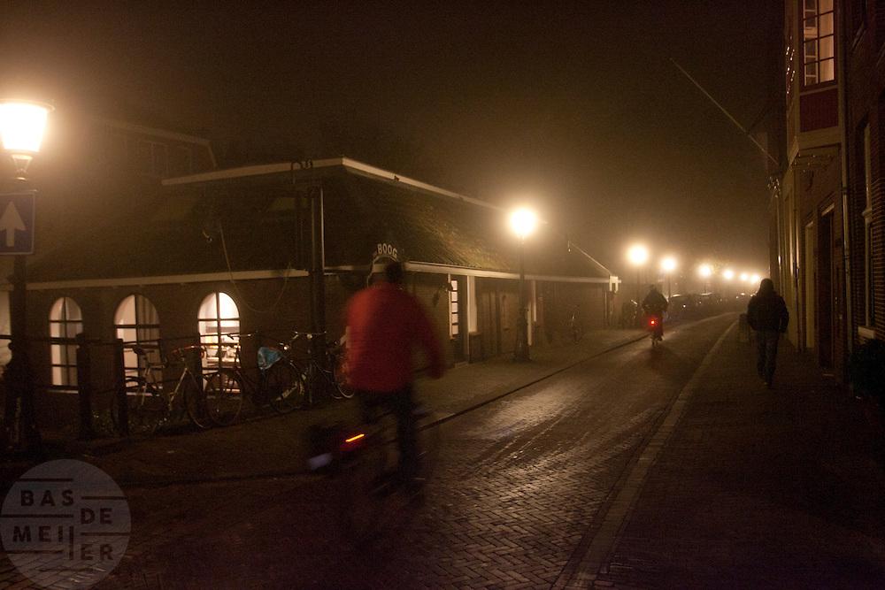Fietsers rijden door de avondmist in Utrecht.<br /> <br /> Cyclist are riding at night with fog