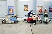 Three men sitting on motor scooters parked in front of wall with vintage posters.