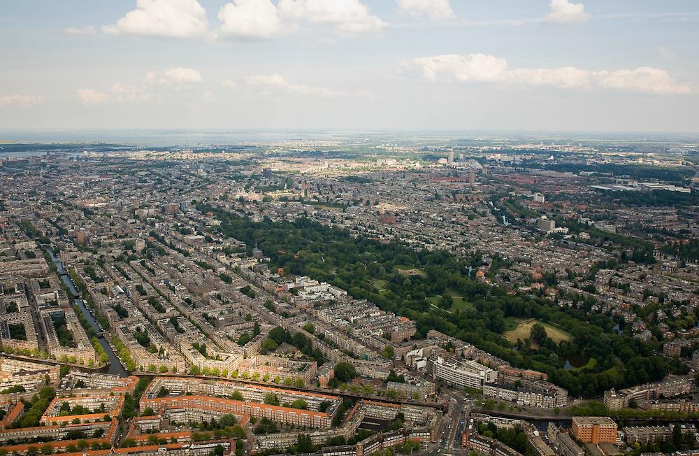 Nederland, Amsterdam, Oud-Zuid, 17-06-2008; overzicht van Oud-West: onder in beeld Surinameplein en brug over de Kostverlorenkade, begin van de Overtoom (diagonaal naar links / het midden); rechts van de Overtoom het Vondelpark en Oud-Zuid; het water links (en naar boven toe)is de Jacob van Lennep kade; buurten die in beeld komen zijn onder andere: Van Lennepbuurt, Helmersbuurt, Overtoomse Sluis / Cremerbuurt, Vondelbuurt; de foto strekt zich uit tot IJburg (in het midden in de zon) en het IJsselmeer.overview Amsterdam West, building blocks and park (Vondelpark).luchtfoto (toeslag); aerial photo (additional fee required); .foto Siebe Swart / photo Siebe Swart