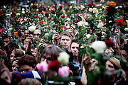 Oslo, Norway, 25.07.2011. An initiative on facebook by a citizen of Oslo resulted after only a few hours that aproximately 200.000 citizens of Oslo met in Rådhusplassen, a square by the harbour to honour the inocent civilans massacred on friday 23. of july. The Prime minister Jens Stoltenberg, along with his coalition government as well the royal family and high profile norwegian artist performing on stage. As the summer in Norway never gets really dark, people brought roses instead of torches. Foto: Christopher Olssøn.