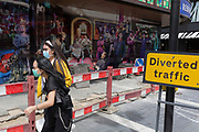 During the UK's Coronavirus pandemic lockdown and on the day when a further 255 deaths occurred, bringing the official covid deaths to 37,048, <br /> young Chinese women wearing face masks walk near a billboard with the characters of many musical productions outside the Sondheim Theatre on Wardour Street, still closed as per governmental rules, on 26th May 2020, in London, England. Theatres and other entertainment venues will be some of the last businesses to re-open as the UK pandemic lockdown improves and many theatres are already close to financial collapse. Lockdown has allowed some roadworks and construction to continue unhindered.