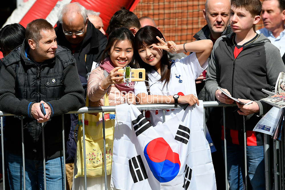 Two girls have a selfie with a Korean flag as they wait for the Tottenham team bus to arrive before the Premier League match between Bournemouth and Tottenham Hotspur at the Vitality Stadium, Bournemouth, England on 4 May 2019.