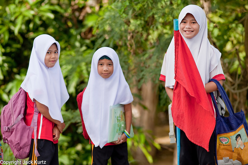 "Sept. 27, 2009 -- PATTANI, THAILAND: Muslim girls on their way to school in Pattani, Thailand, Sept 27. Schools and school teachers have been frequent targets of Muslim insurgents in southern Thailand and the army now provides security at many government schools.  Thailand's three southern most provinces; Yala, Pattani and Narathiwat are often called ""restive"" and a decades long Muslim insurgency has gained traction recently. Nearly 4,000 people have been killed since 2004. The three southern provinces are under emergency control and there are more than 60,000 Thai military, police and paramilitary militia forces trying to keep the peace battling insurgents who favor car bombs and assassination.  Photo by Jack Kurtz / ZUMA Press"