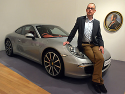 © Licensed to London News Pictures. 15/11/2012. London, UK Mattias Kulla sits on the bonnet of a Porsche 991 which he and his design team created in 2011, the RCA has a long history of its students being employed by Porsche.  The Royal College of Art is celebrating its 175thanniversary with a major exhibition featuring more than 350 works of art and design by over 180 RCA graduates and staff, including Henry Moore, Barbara Hepworth, Tracey Emin, David Hockney, Peter Blake, Bridget Riley and Lucian Freud. The RCA is the world's oldest art and design university in continuous operation. Its first students comprised a small group of teenage boys; today it educates some 1,200 postgraduate students from 55 different countries.. Photo credit : Stephen Simpson/LNP