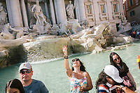 """ROME, ITALY - 20 JUNE 2017: A tourist thows a coin in the Trevi Fountain in Rome, Italy, on June 20th 2017.<br /> <br /> The warm weather has brought a menacing whiff of tourists behaving badly in Rome. On April 12, a man went skinny-dipping in the Trevi fountain resulting in a viral web video and a 500 euro fine.<br /> <br /> Virginia Raggi, the mayor of Rome and a national figurehead of the anti-establishment Five Star Movement,  issued an ordinance involving harsher fines for eating, drinking or sitting on the fountains, for washing animals or clothes in the fountain water or for throwing anything other than coins into the water of the Trevi Fountain, Bernini's Four Fountains and 35 other city fountains of artistic or historic significance around the city.  """"It is unacceptable that someone use them to go swimming or clean themselves, it's an historic patrimony that we must safeguard,"""" Ms. Raggi said."""