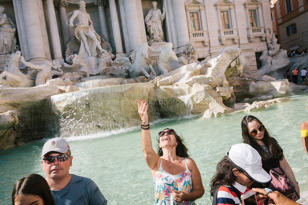 ROME, ITALY - 20 JUNE 2017: A tourist thows a coin in the Trevi Fountain in Rome, Italy, on June 20th 2017.<br /> <br /> The warm weather has brought a menacing whiff of tourists behaving badly in Rome. On April 12, a man went skinny-dipping in the Trevi fountain resulting in a viral web video and a 500 euro fine.<br /> <br /> Virginia Raggi, the mayor of Rome and a national figurehead of the anti-establishment Five Star Movement,  issued an ordinance involving harsher fines for eating, drinking or sitting on the fountains, for washing animals or clothes in the fountain water or for throwing anything other than coins into the water of the Trevi Fountain, Bernini&rsquo;s Four Fountains and 35 other city fountains of artistic or historic significance around the city.  &ldquo;It is unacceptable that someone use them to go swimming or clean themselves, it&rsquo;s an historic patrimony that we must safeguard,&rdquo; Ms. Raggi said.