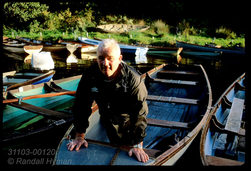 Patrick Hegarty poses aboard boat docked with others in slough off Ross Bay in Killarney National Park, Ireland.