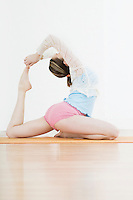 Teenage girl (16-17) performing yoga