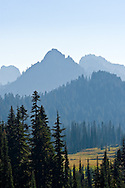 Lane and Waypenayo Peaks in the Tatoosh Range partly obscured by wildfire smoke in Paradise Valley.  Photographed from Mount Rainier National Park in Washington State, USA.