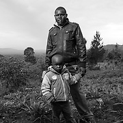William Lokir stands with his son, Elias Korir. William's wife, Leah Lokir, died on February 19, 2018 while giving birth to their baby Bahati Chesista on March 2, 2018 in Chepareria, West Pokot, Kenya. William is now the caretaker of their 8 children.
