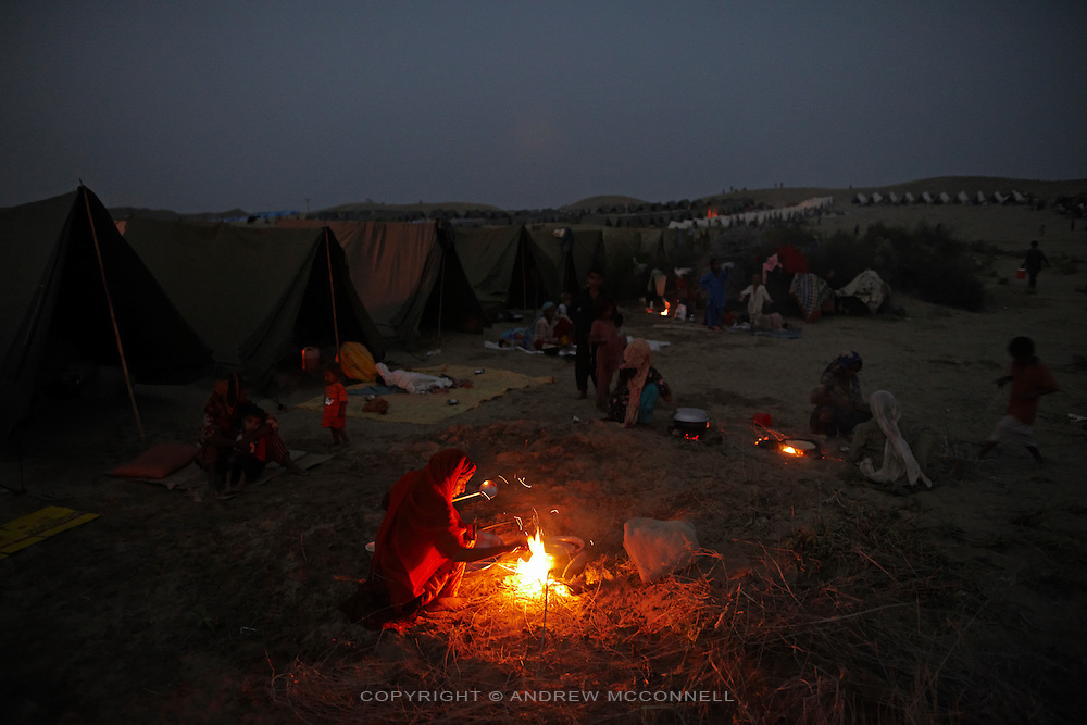 People cooks on fires at a camp for those displaced by the floods, near Sehwan, in Sindh province, Pakistan.