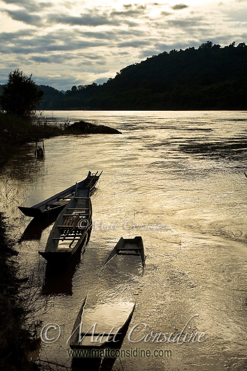 Wooden fishing boats and the golden Mekong river at sunset.<br /> (Photo by Matt Considine - Images of Asia Collection)