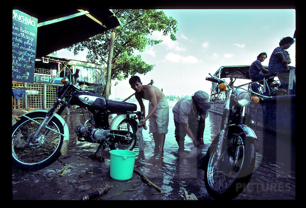 Two vietnamese men washes their Honda 67 along the Bassac River, Can Tho, Vietnam, Southeast Asia, 1997