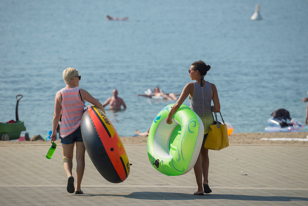 Canada, British Columbia,Okanagan Valley, Kelowna, two women with floating devices heading to the beach