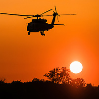 A military helicopter flies above the tree line along the Potomac River at sundown in Washington, DC, Thursday, May 19, 2016.