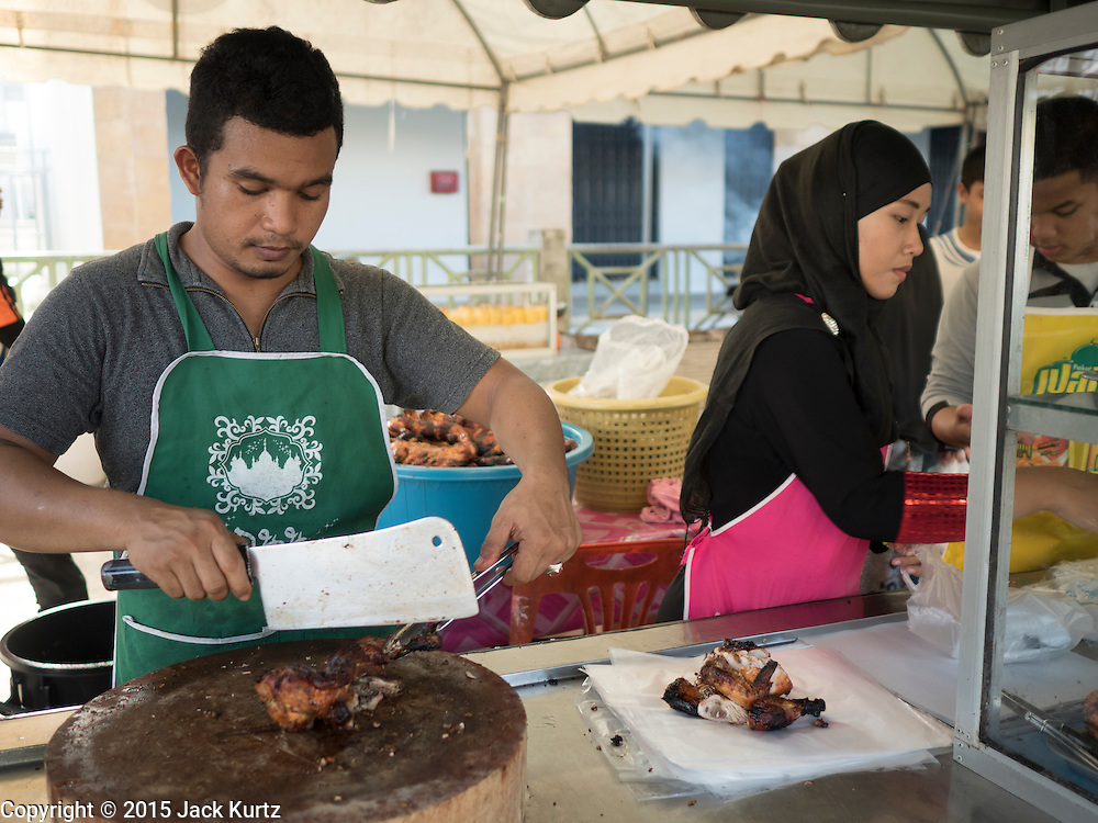 18 JUNE 2015 - PATTANI, PATTANI, THAILAND:  Muslim vendors cut up barbecued chicken at the Ramadan Bazaar in Pattani. People come to the street food market late in the day to buy meals for the evening Iftar meal, which breaks the day long fast. Ramadan is the ninth month of the Islamic calendar, and is observed by Muslims worldwide as a month of fasting to commemorate the first revelation of the Quran to Muhammad according to Islamic belief. This annual observance is regarded as one of the Five Pillars of Islam. Islam is the second largest religion in Thailand. Pattani, along with Narathiwat and Yala provinces, all on the Malaysian border, have a Muslim majority.       PHOTO BY JACK KURTZ