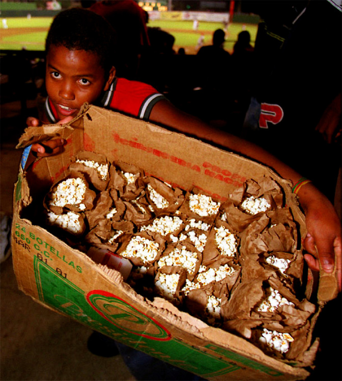 During the baseball game young vendors sell popcorn from a empty beer bottle box in small paper bags.