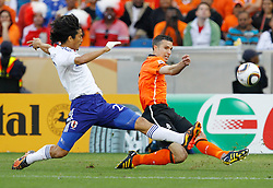 Robin van Persie (r, Holland) and Yuji Nakazawa  (l, Japan) during the 2010 FIFA World Cup South Africa Group E match between Netherlands and Japan at Durban Stadium on June 19, 2010 in Durban, South Africa.
