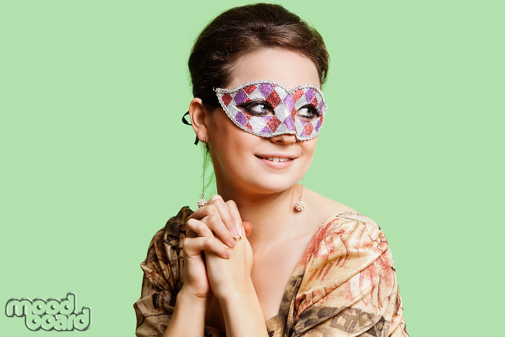 Portrait of beautiful young woman with eye mask day dreaming against green background