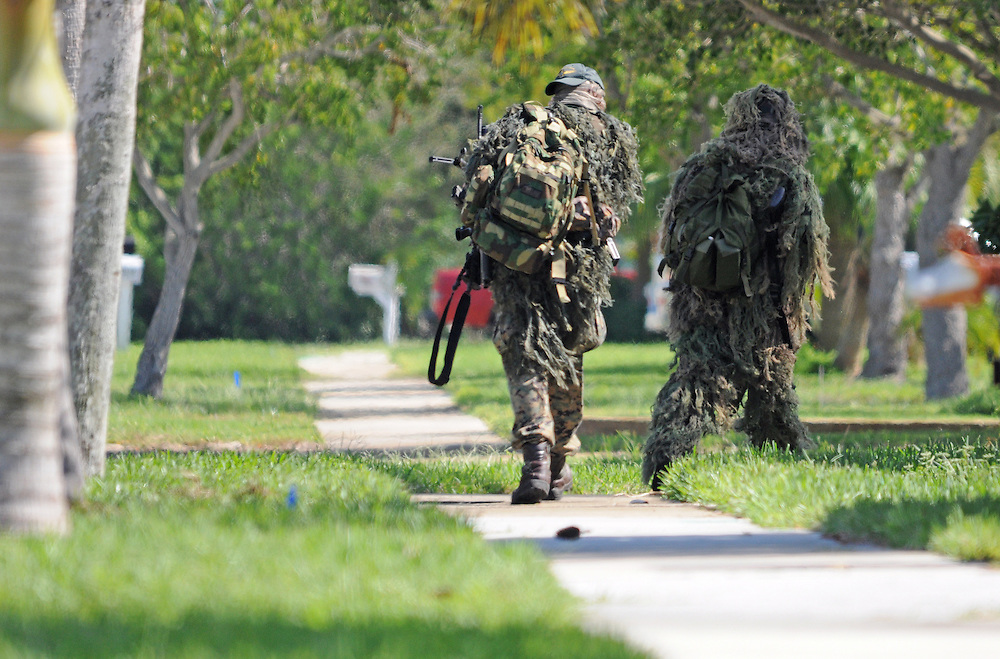 Andrew Knapp, FLORIDA TODAY -- Oct. 20, 2011 -- SWAT team members and sheriff's deputies get into position Thursday during a standoff with a resident on Barr Street on Merritt Island.