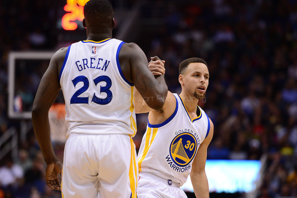 Feb 10, 2016; Phoenix, AZ, USA; Golden State Warriors guard Stephen Curry (30) is helped up by teammate forward Draymond Green (23) during the game against the Phoenix Suns at Talking Stick Resort Arena. The Golden State Warriors won 112-104. Mandatory Credit: Jennifer Stewart-USA TODAY Sports
