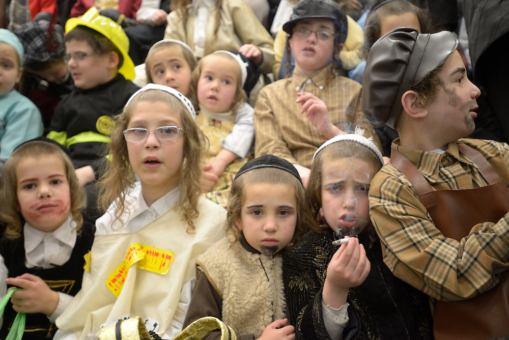 JERUSALEM, ISRAEL - MARCH 17, 2014: Ultra-Orthodox Jewish kids, some of them smoking cigarettesm, celebrate the Purim holiday in the ultra-orthodox Mea Shearim neighborhood in Jerusalem on March 17, 2014. The festival of Purim commemorates the rescue of Jews from a genocide in ancient Persia. Photo by Gili Yaari