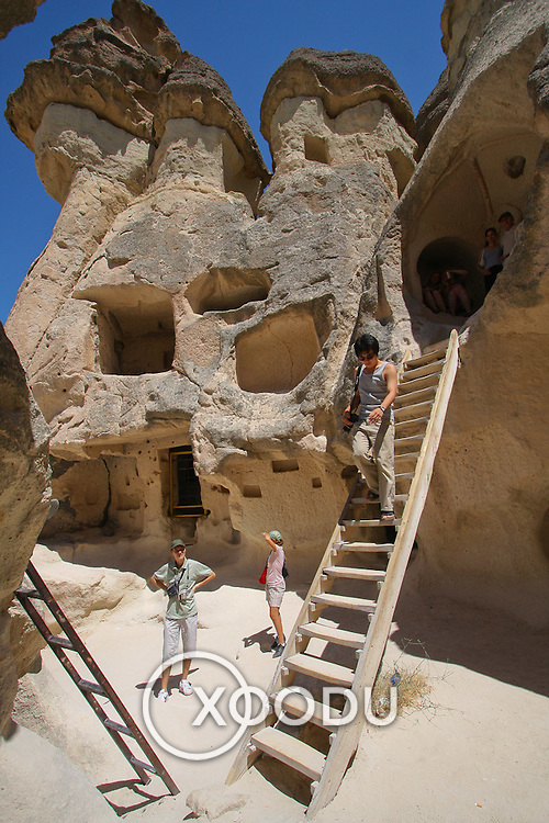 Tourist climbs ladder at Pasabag (Goreme, Turkey - Jul. 2008) (Image ID: 080718-1130571a)