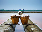 28 MARCH 2018 - BAN LAEM, PHETCHABURI, THAILAND:  Baskets of salt in the field during the 2018 salt harvest in Petchaburi province, about two hours south of Bangkok. Sea salt is made in provinces south of Bangkok by flooding fields with ocean water after the rainy season. As the fields dry out from evaporation, workers go into the fields and gather the salt left behind.       PHOTO BY JACK KURTZ