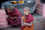 "Samanera in Bodhgaya, India. In Pali lenguage, the word  samanera, means 'small monk' or 'boy monk. Even if very young, they have to adopt part of the monastic code and study the canonical texts ""Vinaya"" in preparation for full ordination."
