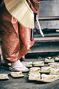 A traditionally dressed participant puts on his geta, a traditional Japanese footwear.