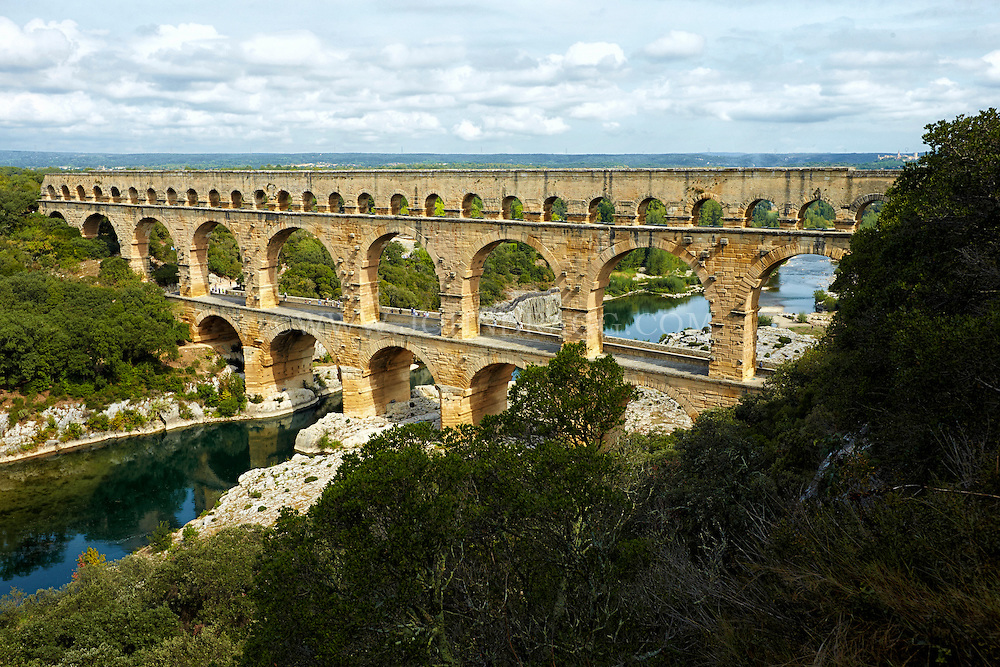 View of Pont du Gard (Roman Aqueduct), the reflective Gardon River, and Garrigue Natural Area, Vers-Pont-du-Gard, France.