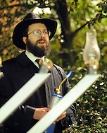 """DOYLESTOWN, PA - DECEMBER 16: Rabbi Mendel Prus of the Lubavitch of Doylestown speaks to the crowd before lighting a menorah during a Hanukkah  celebration at the Bucks County Courthouse December 16, 2014 in Doylestown, Pennsylvania. After the lighting of the menorah, the group continued the celebration of the """"festival of lights"""" inside the courthouse. (Photo by William Thomas Cain/Cain Images)"""