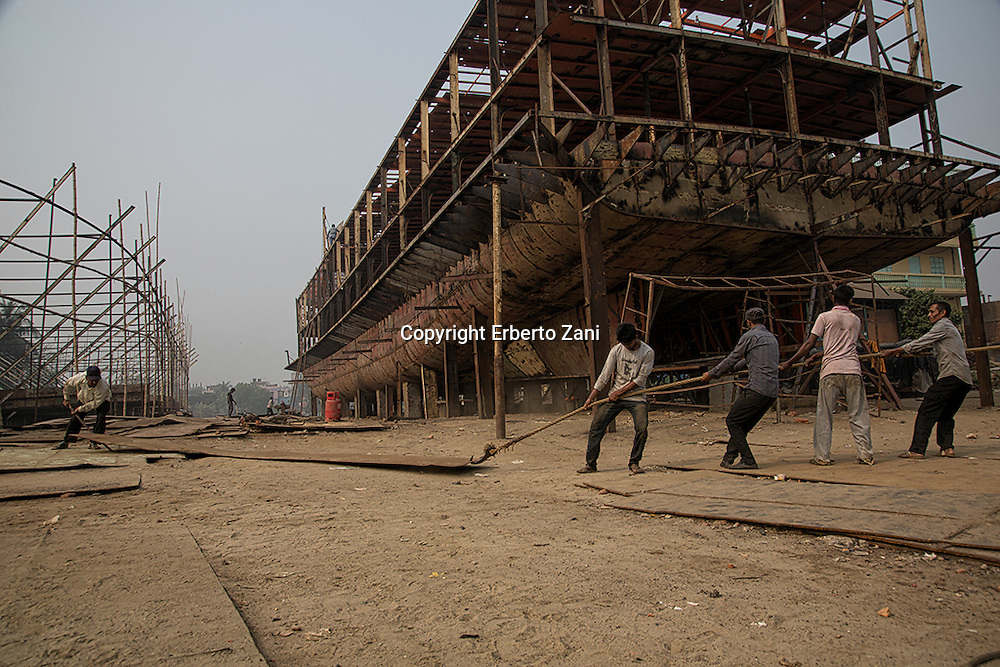 Ship breaking, and rebuilding, yards in Bangladesh: in Dhaka, long river Buriganga irremediably contaminated by fuel waste left in the tanks and by heavy metals, big sections are removed by explosives and cut with blow torches. A huge helix, half-buried in front of me, makes me realize the proportions of these giants of the sea and the backbreaking work of dismantling made barehanded by thousands of workers. <br />