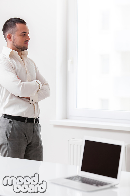 Businessman staring out of window with laptop in foreground
