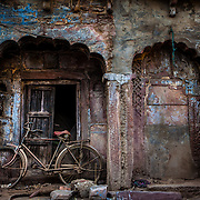 An old bicycle blends into the surrounding of a dilapidated old building.
