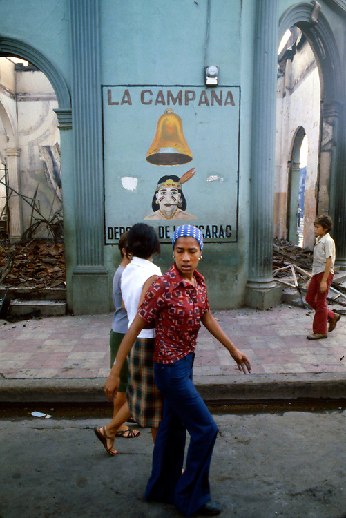 Young refugees of the Civil War in Nicaragua walk past businesses attacked and burned by government National Guard troops during the 1978 civil war. Civil War in Nicaragua - 1978
