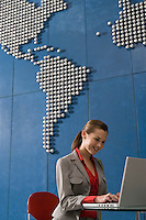 Business woman using laptop in office with world map on wall