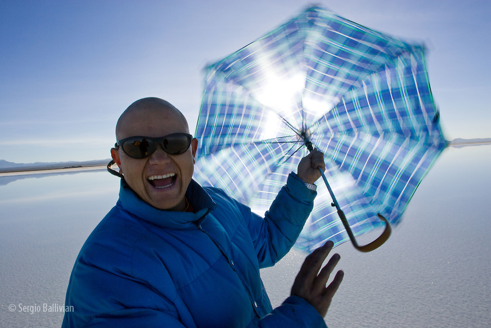 A bald man spins an umbrella as he protects himself from the harsh Andean Sun in the flooded Salar de Uyuni near Colchani, Bolivia.