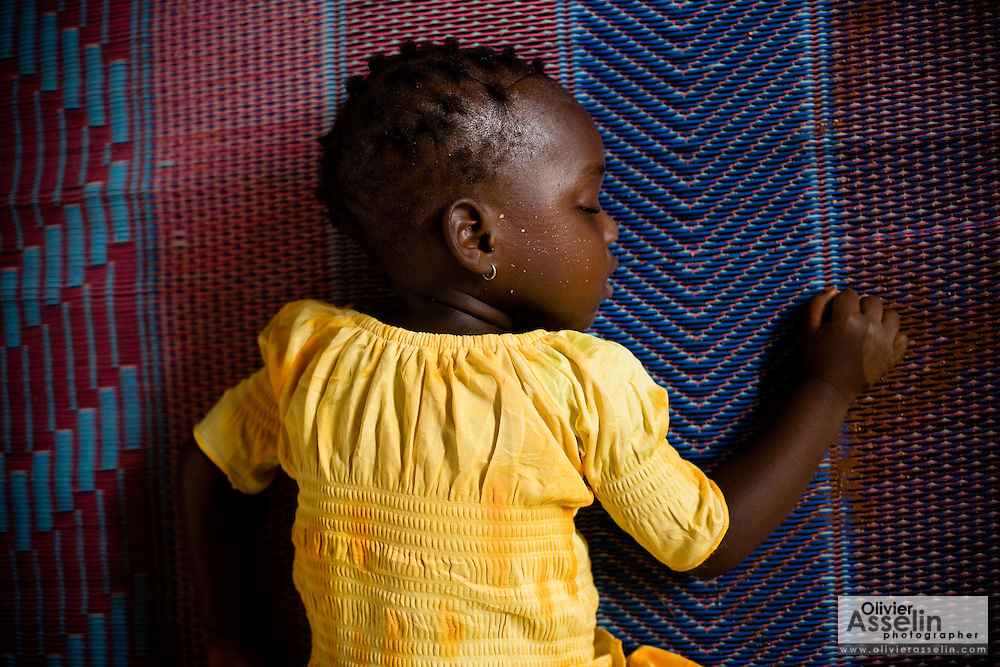A young girl sleeps on a floor mat at the Alandohou primary school in the village of Alandohou, Benin on Monday September 10, 2007.