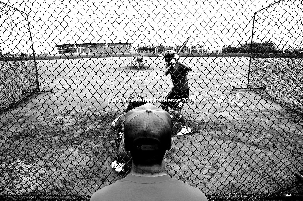 BEIJING, JULY -18: Yi Sheng, (L), trainer with the national baseball team, watches his players at practise in the field, Beijing, July 18, 2007, China.