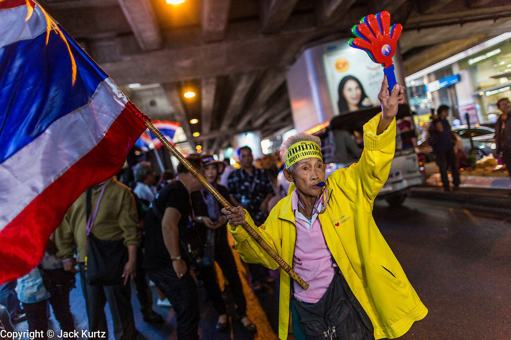 "20 DECEMBER 2013 - BANGKOK, THAILAND: An elderly anti-government protestor walks down Silom Road. Thousands of anti-government protestors, supporters of the so called Peoples Democratic Reform Committee (PRDC), jammed the Silom area, the ""Wall Street"" of Bangkok, Friday as a part of the ongoing protests against the caretaker government of Yingluck Shinawatra. Yingluck dissolved the Thai Parliament earlier this month and called for national elections on Feb. 2, 2014. The protestors want the elections postponed and the caretaker government to step down. The Thai election commission ruled Friday that the election would go on dispite the protests.          PHOTO BY JACK KURTZ"