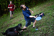 Peter Bolduc, of West Lebanon, side arms a disc up a steep fairway on the Storrs Pond disc golf course despite the playing dogs of fellow disc golfers James Beaulieu, left, and Spencer Weatherholt, not pictured, in Hanover, N.H. Thursday, May 21, 2015. Steeply contoured terrain and fairways with obstacles combine to create a challenging course. (Valley News - James M. Patterson)<br /> Copyright &copy; Valley News. May not be reprinted or used online without permission. Send requests to permission@vnews.com.